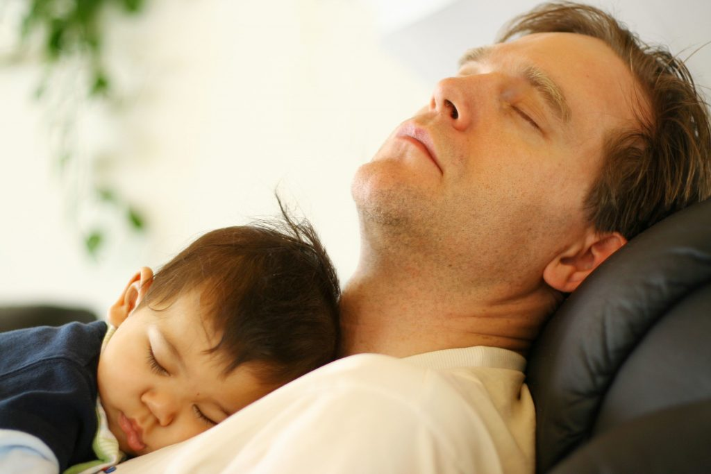 baby and father sleeping in recliner chair